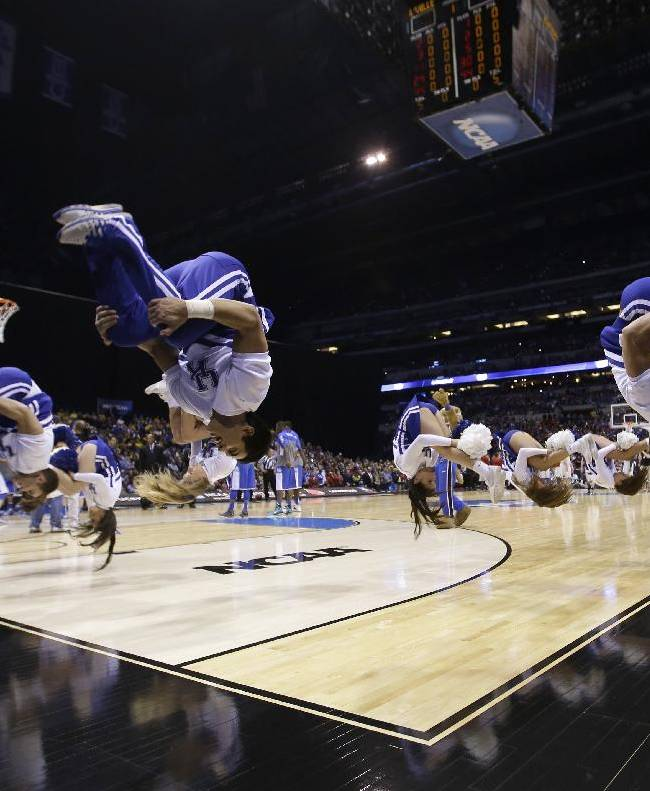 Kentucky cheerleaders flip before an NCAA Midwest Regional semifinal college basketball tournament game against the Louisville Friday, March 28, 2014, in Indianapolis