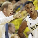 FILE - In this Jan. 6, 2013, file photo, Michigan head coach John Beilein, left, talks with guard Trey Burke (3) during the first half of an NCAA college basketball game against Iowa at Crisler Arena in Ann Arbor, Mich. They've earned the admiration of their Fab Five predecessors and even grudging respect from Tom Izzo, but after moving to No. 1, the Wolverines still have a lot to prove.  (AP Photo/Carlos Osorio, File)
