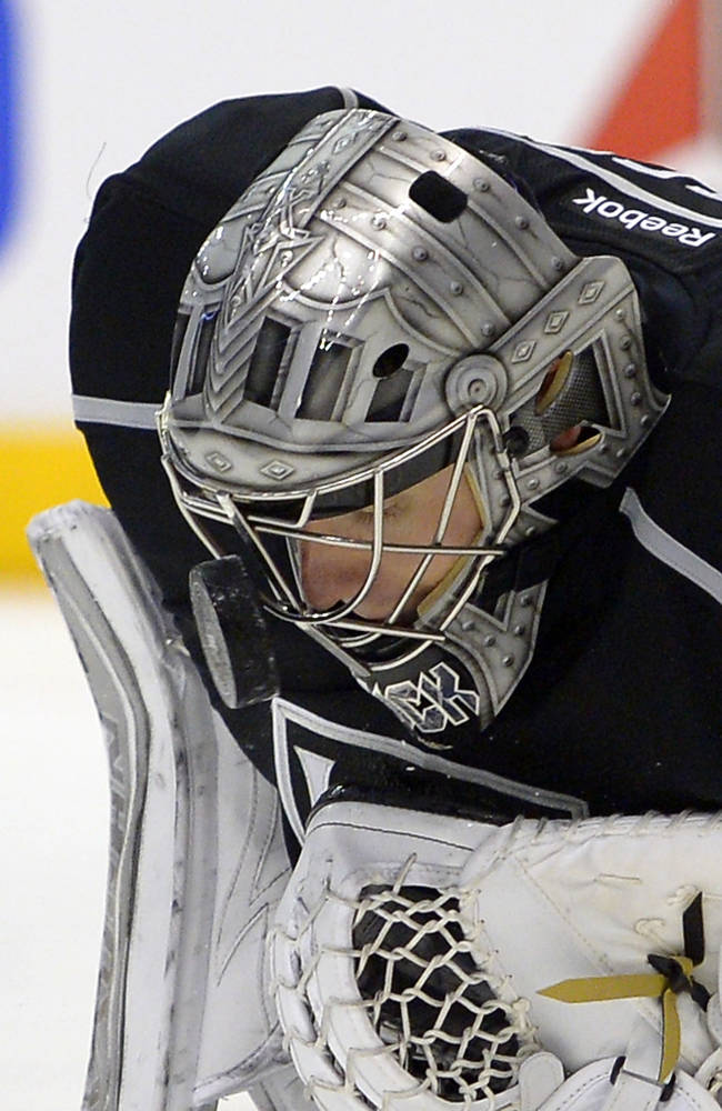 Los Angeles Kings goalie Jonathan Quick stops a shot with his mask during the first period of an NHL hockey game against the Carolina Hurricanes, Saturday, March 1, 2014, in Los Angeles