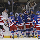 New York Rangers left wing Ryan Malone (24), second from right, celebrates after scoring on New Jersey Devils goalie Scott Clemmensen (40) during the first period of their preseason NHL hockey game, Monday, Sept. 22, 2014, in New York The Associated Press