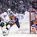 Los Angeles Kings Marian Gaborik (12) and Edmonton Oilers Justin Schultz (19) battle for the puck as goalie Ben Scrivens (30) protects the net during first period NHL hockey action in Edmonton, Canada, Sunday March 9, 2014 The Associated Press