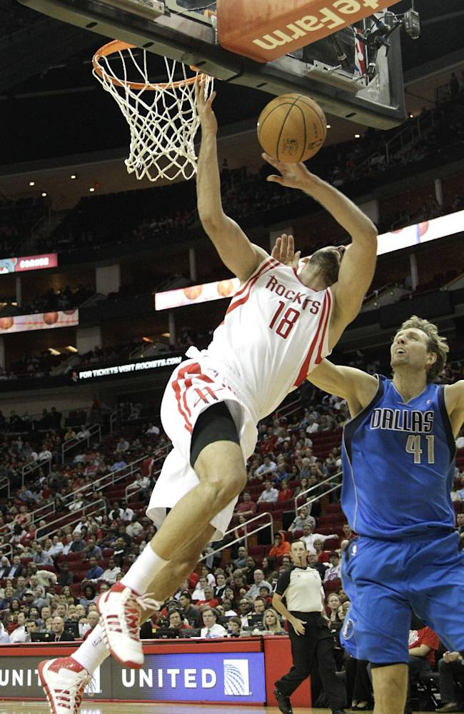 Houston Rocket's Omri Casspi, left, is fouled by Dallas Maverick's Dirk Nowitzki, right, as he drives to the basket in the second half of a preseason NBA basketball game Monday, Oct. 21, 2013, in Houston. Nowitzki was called for a flagrant two foul and was ejected from the game. Houston won 100-95