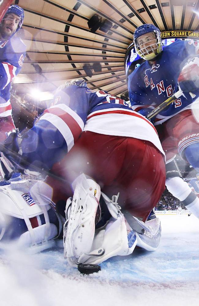 New York Rangers goalie Henrik Lundqvist looks for the puck behind him near the goal line as center Derek Stepan, right, moves in to help in the third period against the Los Angeles Kings during Game 4 of the NHL hockey Stanley Cup Final, Wednesday, June 11, 2014, in New York. Rangers Dan Girardi is at left. The Rangers won 2-1