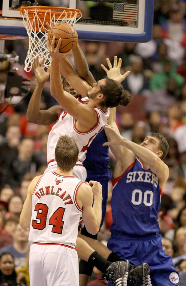 Chicago Bulls' Joakim Noah (13) goes up for a score as Philadelphia 76ers' Thaddeus Young and Spencer Hawes (00) defend in the second half of an NBA basketball game Saturday Nov. 2, 2013, in Philadelphia. The 76ers won 107-104