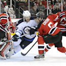 New Jersey Devils' Andy Greene (6) checks Winnipeg Jets' Matt Halischuk into Devils goaltender Martin Brodeur, left, during the first period of an NHL hockey game Monday, Nov. 25, 2013, in Newark, N.J The Associated Press