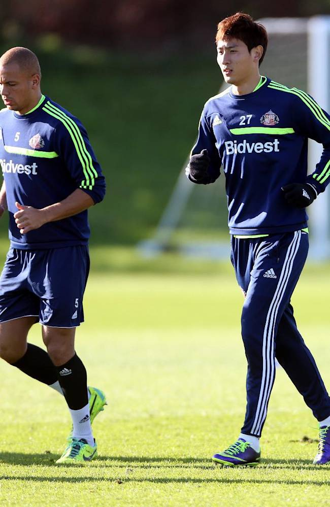 Sunderland's Wes Brown, left, and Ji Dong-Won, right, during a training session at the club training ground, Sunderland, England, Thursday Oct. 24, 2013. Sunderland will play Newcastle United in a Premier League match on Sunday