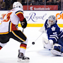 Toronto Maple Leafs goalie Jonathan Bernier (45) makes a save against Calgary Flames forward Johnny Gaudreau (13) during the first period of an NHL hockey game in Toronto on Tuesday, Dec. 9, 2014 The Associated Press
