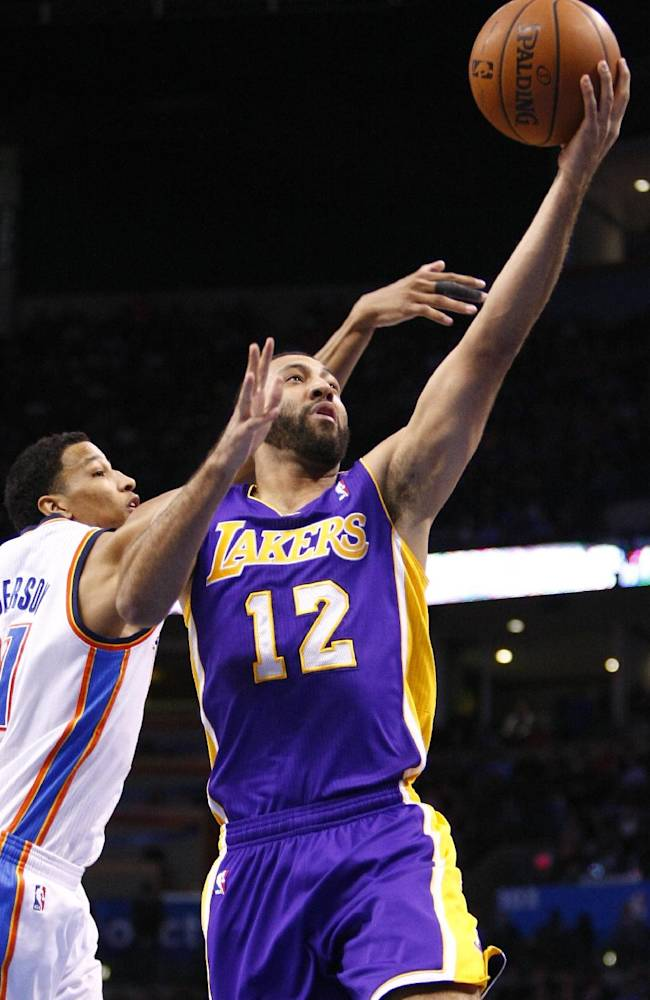 Los Angeles Lakers guard Kendall Marshall (12) goes to the basket in front of Oklahoma City Thunder guard Andre Roberson (21) during the first quarter of an NBA basketball game in Oklahoma City, Thursday, March 13, 2014