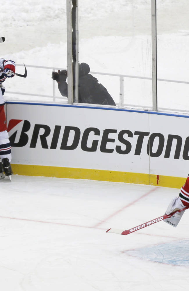 The New York Rangers celebrate a goal by Dominic Moore as New Jersey Devils goalie Martin Brodeur (30) reacts  during the first period of an outdoor NHL hockey game Sunday, Jan. 26, 2014, at Yankee Stadium in New York