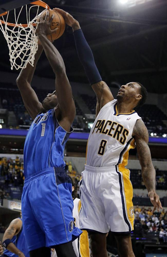 Dallas Mavericks center Samuel Dalembert, left, has his shot blocked by Indiana Pacers guard Rasual Butler during the first half of an NBA preseason basketball game in Indianapolis, Wednesday, Oct. 16, 2013