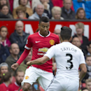 Manchester United's Jesse Lingard, left, keeps the ball from Swansea City's Neil Taylor during their English Premier League soccer match at Old Trafford Stadium, Manchester, England, Saturday Aug. 16, 2014