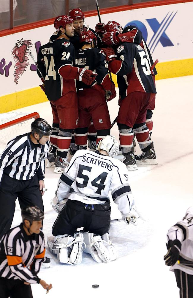 The Phoenix Coyotes celebrate a goal by Derek Morris as Los Angeles Kings goalie Ben Scrivens (54) stands up during the second period of an NHL hockey game, Tuesday, Oct. 29, 2013, in Glendale, Ariz