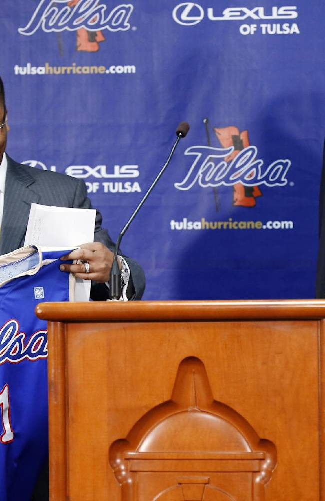 Tulsa's new men's basketball coach Frank Haith holds a uniform as he stands near the podium with athletic director Derrick Gragg at a news conference Friday, April 18, 2014, in Tulsa, Okla