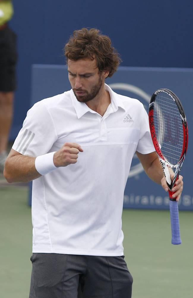 Ernests Gulbis, from Latvia, reacts during a first round match with Ivan Dodig, from Croatia, at the Western & Southern Open tennis tournament, Tuesday, Aug. 12, 2014, in Mason, Ohio