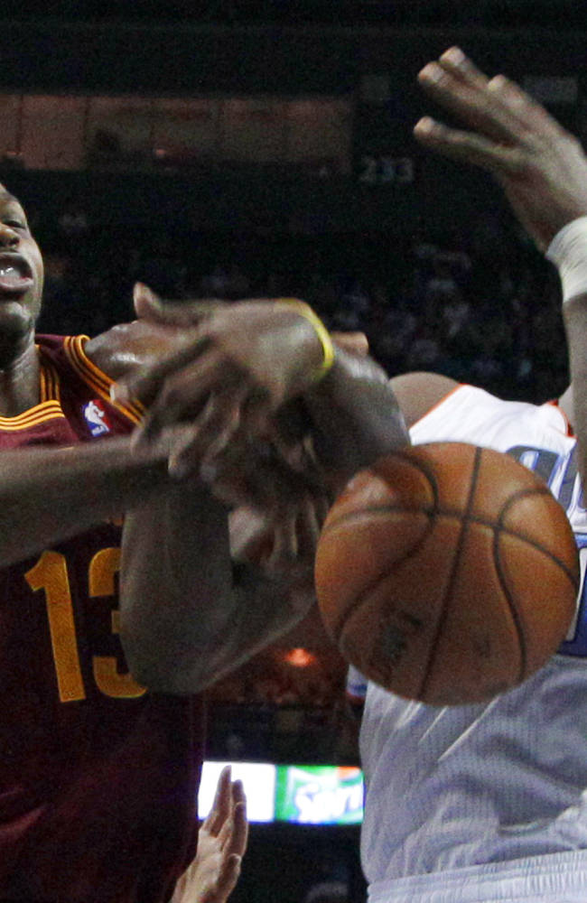 Charlotte Bobcats' Bismack Biyombo, right, and Cleveland Cavaliers' Tristan Thompson, left, battle for a rebound in the first half of an NBA basketball game in Charlotte, N.C., Friday, Nov. 1, 2013