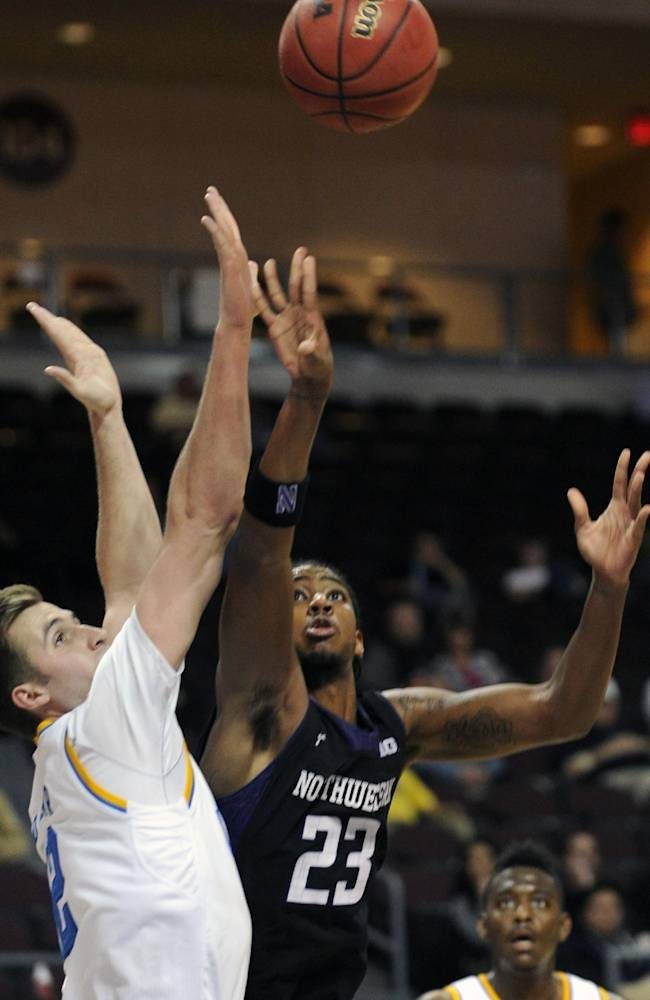 UCLA's David Wear, left, defends as Northwestern's JerShon Cobb (23) shoots during the second half of an NCAA college basketball game at the Las Vegas Invitational on Friday, Nov. 29, 2013, in Las Vegas. UCLA won 95-79