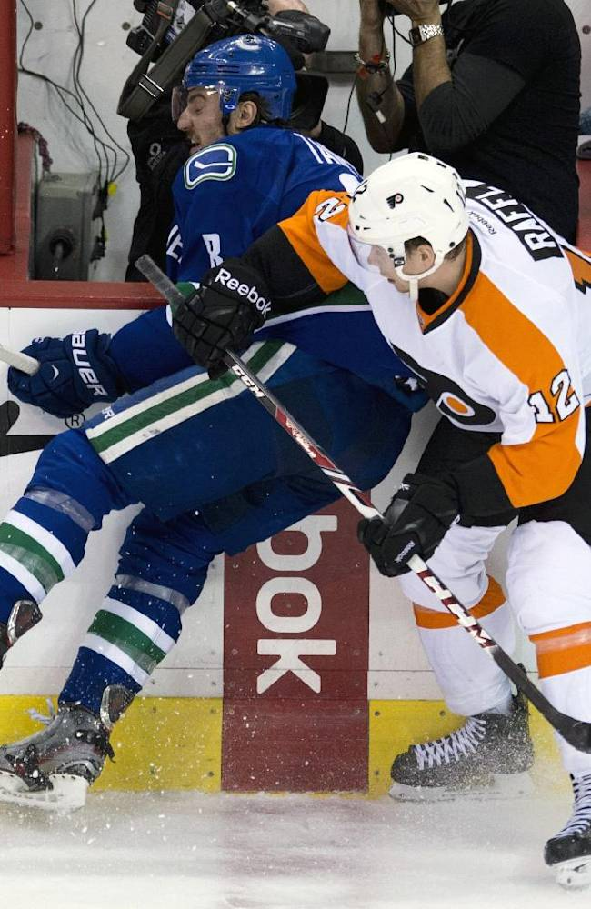 Philadelphia Flyers left wing Michael Raffl (12) puts Vancouver Canucks defenseman Chris Tanev (8) into the boards during the first period of an NHL hockey game against the Philadelphia Flyers in Vancouver, British Columbia, Monday, Dec. 30, 2013