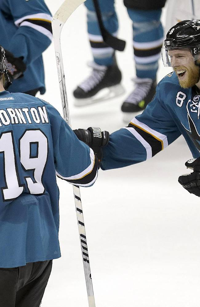 CORRECTS SCORE - San Jose Sharks center Joe Pavelski (8) congratulates center Joe Thornton (19) after a 2-1 shoot out victory against the Chicago Blackhawks in a NHL hockey game in San Jose, Calif., Saturday, Feb. 1, 2014