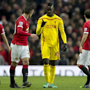 Liverpool's Mario Balotelli, centre gestures to Manchester United's Robin van Persie during the English Premier League soccer match between Manchester United and Liverpool at Old Trafford Stadium, Manchester, England, Sunday Dec. 14, 2014