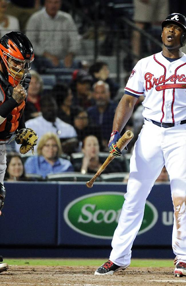 San Francisco Giants catcher Hector Sanchez, left, clenches his fist as Atlanta Braves' Justin Upton, right, strikes out to end the ninth inning of a baseball game Friday, May 2, 2014, in Atlanta. San Francisco won 2-1
