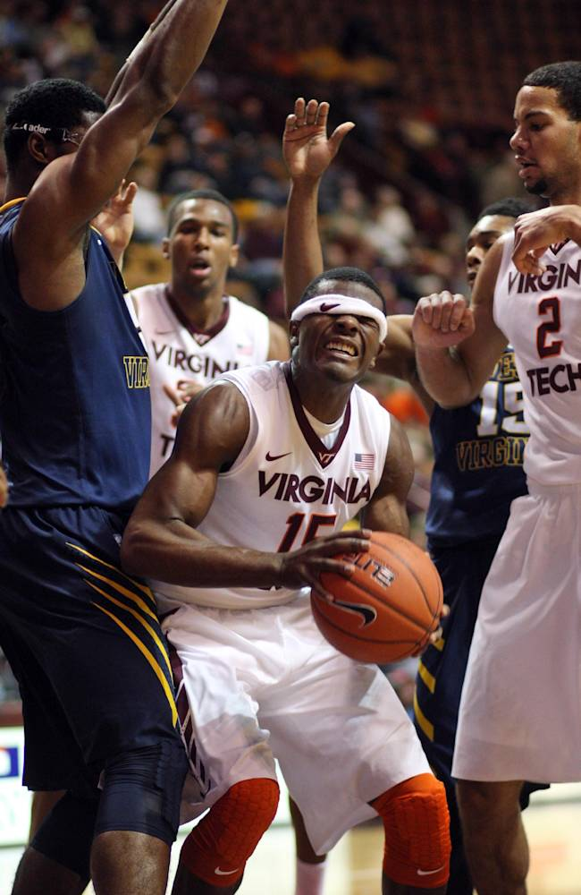 Virginia Tech guard Ben Emelogu (15) struggles with his headband under the basket during the first half of an NCAA college basketball game against West Virginia, in Blacksburg, Va., Tuesday, Nov. 12, 2013