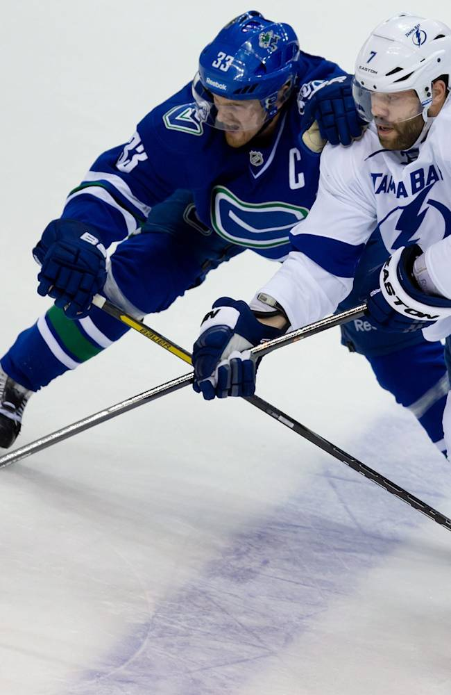 Tampa Bay Lightning's Radko Gudas, right, of the Czech Republic, passes while being checked by Vancouver Canucks' Henrik Sedin, of Sweden, during an NHL hockey game Wednesday, Jan. 1, 2014, in Vancouver, British Columbia