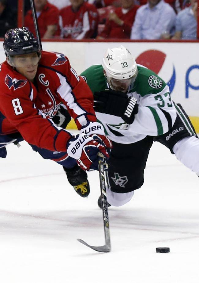 Washington Capitals right wing Alex Ovechkin (8), from Russia, tries to shoot as he is guarded by Dallas Stars defenseman Alex Goligoski (33) in the first period of an NHL hockey game, Tuesday, April 1, 2014, in Washington