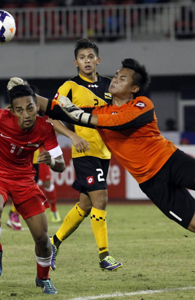 Abdul Hafiz Abdul Rahim, right, goalkeeper of Brunei, tries to catch the ball next to Muhammad Fariz Ramli, left, of Singapore, during their soccer match at the 27th SEA Games in Naypyitaw, Myanmar, Friday, Dec. 13, 2013. Singapore beat Brunei 2-0