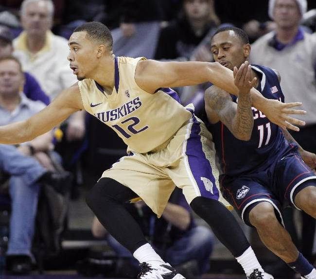 Washington's Andrew Andrews works to control the ball under pressure from Connecticut's Ryan Boatright in the second half of an NCAA college basketball game in Seattle on Sunday, Dec. 22, 2013. UConn won 82-70