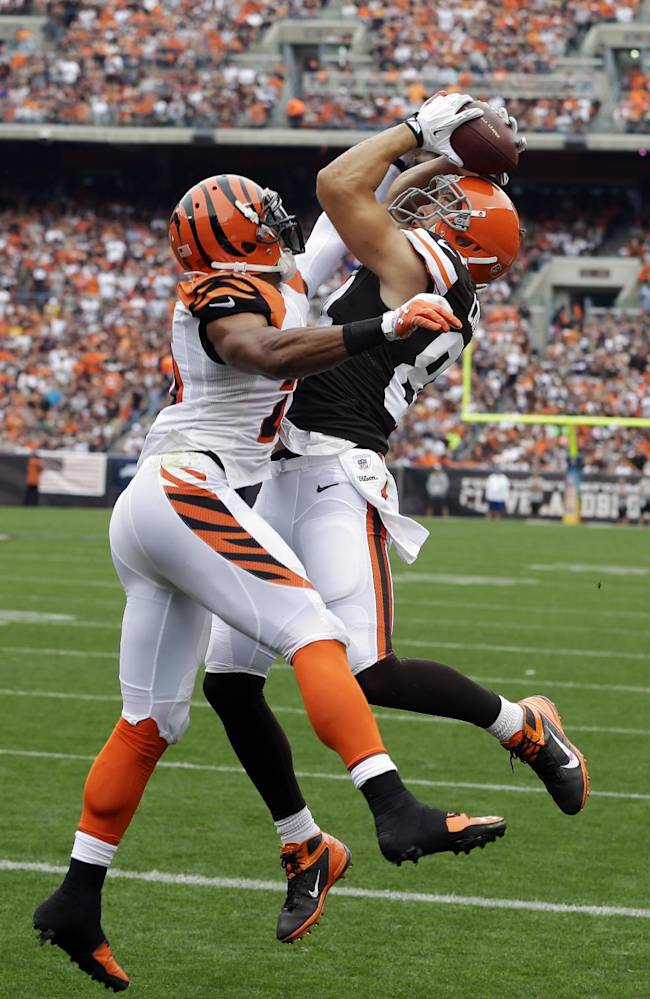 Cleveland Browns tight end Jordan Cameron, right,  makes a leaping catch on a 2-yard touchdown pass against Cincinnati Bengals strong safety Taylor Mays in the first quarter of an NFL football game Sunday, Sept. 29, 2013, in Cleveland