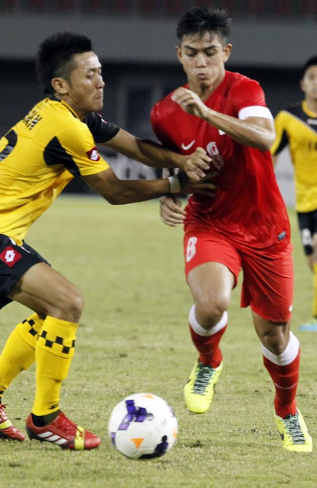 Hazwan Hamzah of Brunei, left, and Muhammad Hafis Abu Sujad of Singapore vie for the ball during their soccer match at the 27th SEA Games at Zayarthiri football stadium in Naypyitaw, Myanmar, Friday, Dec. 13, 2013. Singapore beat Brunei with 2-0
