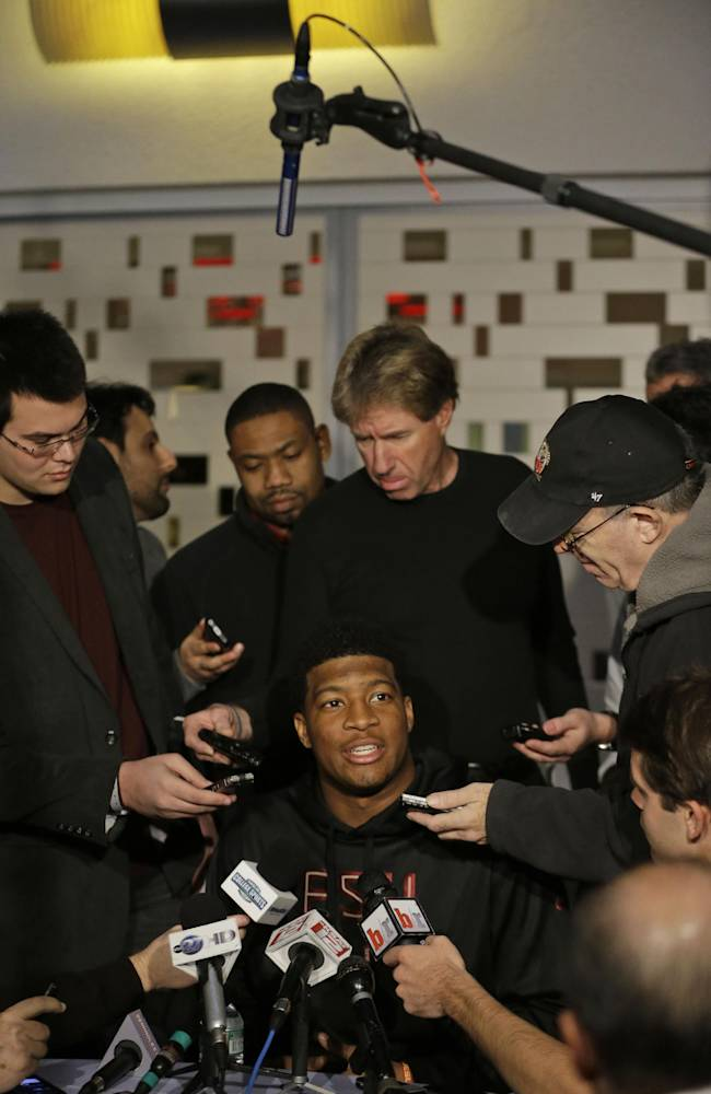 Heisman Trophy finalist Jameis Winston, center, a quarterback at Florida State, talks to  reporters during an informal media availability, Friday, Dec. 13, 2013, in New York
