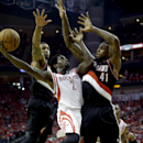 Houston Rockets' Patrick Beverley (2) goes up for a a shot as Portland Trail Blazers' Thomas Robinson (41) and Damian Lillard, left, defend during the third quarter in Game 1 of an opening-round NBA basketball playoff series Sunday, April 20, 2014, in Hou