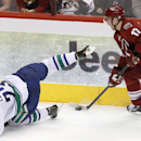 Vancouver Canucks' Alexander Edler (23), of Sweden, falls to the ice as Phoenix Coyotes' Radim Vrbata (17), of the Czech Republic, skates with the puck during the second period of an NHL hockey game on Tuesday, March 4, 2014, in Glendale, Ariz. The Coyote