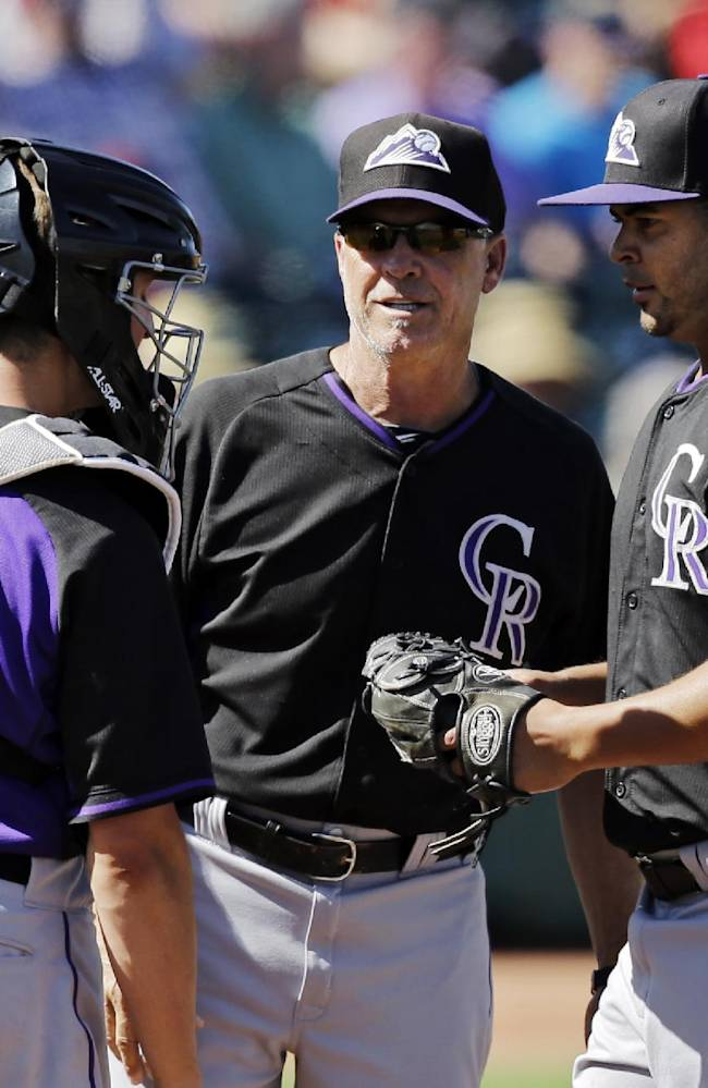 Colorado Rockies bench coach Tom Runnells, center, acting as manager for a split squad game, talks to relief pitcher Leuris Gomez, right, and catcher Jordan Pacheco (58) in the fifth inning of a spring exhibition baseball game Saturday, March 22, 2014, in Goodyear, Ariz