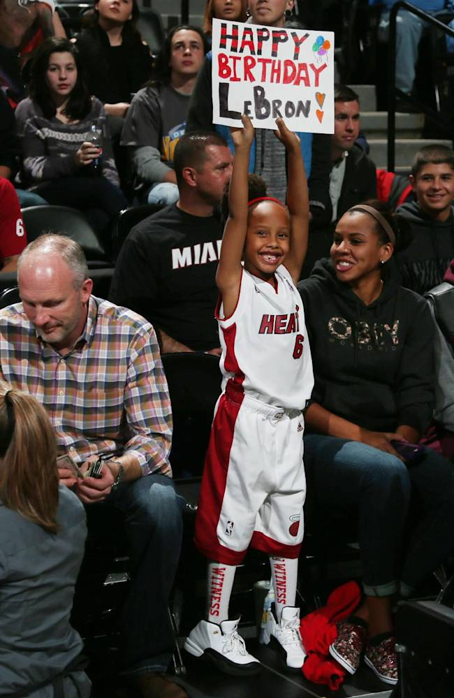 Seven-year-old Jasmine Gipson, of Albuquerque, N.M., holds up a sign to send birthday wishes to her favorite player, Miami Heat forward LeBron James, from a seat behind the Heat bench during the first quart of an NBA basketball game against the Denver Nuggets, Monday, Dec. 30, 2013, in Denver