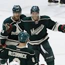 Minnesota Wild center Stephane Veilleux, top right, celebrates with right wing Jason Pominville, top left, and center Cody McCormick (8) after scoring against Pittsburgh Penguins goalie Jeff Zatkoff during the first period of an NHL hockey game in St. Pau