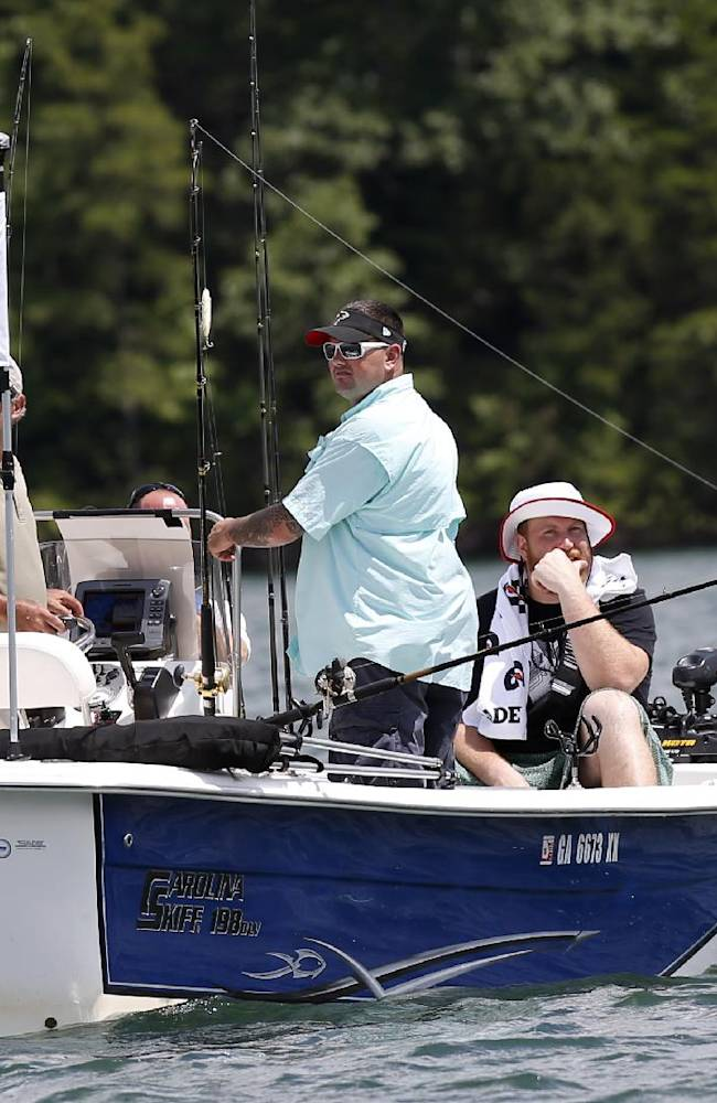 Purple Heart recipient Sgt. Jason Ulin, center, of Savannah, Ga., fishes with Atlanta Falcons' offensive tackle Sam Baker, right, and fishing guide John Mantovani  during the team's annual 'Fishing With the Falcons' event with wounded veterans Wednesday,  June 11, 2014, on Lake Lanier in Buford, Ga. The Falcons host the annual out outing to thank wounded veterans. Ulin served two tours in Afghanistan