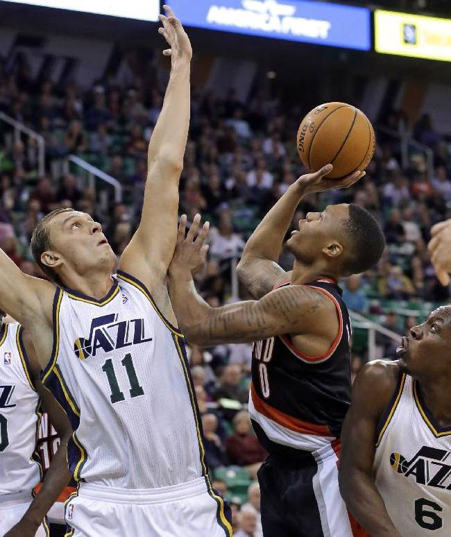 Portland Trail Blazers' Damian Lillard (0) shoots as Utah Jazz's Andris Biedrins (11) defends while Utah'sLester Hudson (6) watches duringthe second quarter of an NBA preseason basketball game Wednesday, Oct. 16, 2013, in Salt Lake City