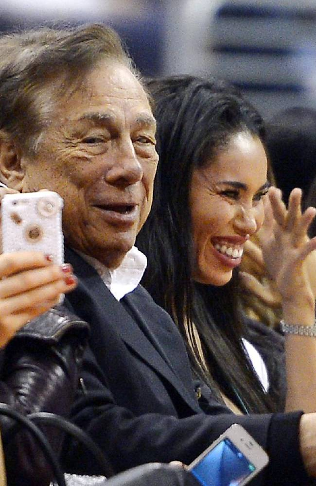 In this photo taken on Friday, Oct. 25, 2013, Los Angeles Clippers owner Donald Sterling, center, and V. Stiviano, right, watch the Clippers play the Sacramento Kings during the first half of an NBA basketball game, in Los Angeles. The NBA is investigating a report of an audio recording in which a man purported to be Sterling makes racist remarks while speaking to his Stiviano.  NBA spokesman Mike Bass said in a statement Saturday, April 26, 2014, that the league is in the process of authenticating the validity of the recording posted on TMZ's website. Bass called the comments