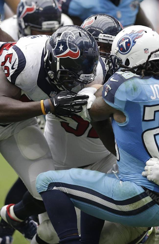 Tennessee Titans' Chris Johnson (28) is brought down for a safety by Houston Texans' Brian Cushing, right, Whitney Mercilus, left, and Earl Mitchell, center, during the fourth quarter of an NFL football game on Sunday, Sept. 15, 2013, in Houston