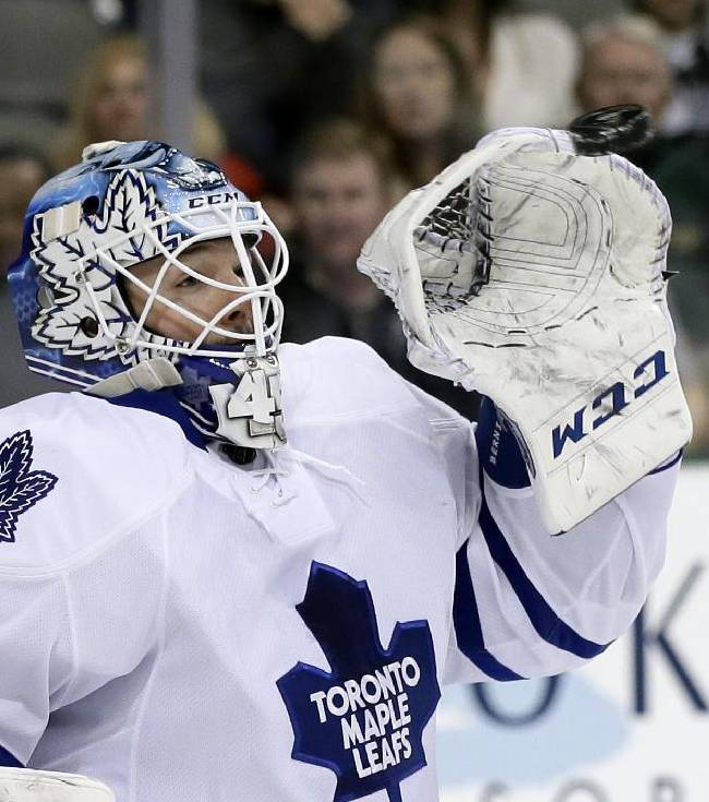Toronto Maple Leafs goalie Jonathan Bernier reaches up to glove a shot from the Dallas Stars in the first period of an NHL hockey game, Thursday, Jan. 23, 2014, in Dallas