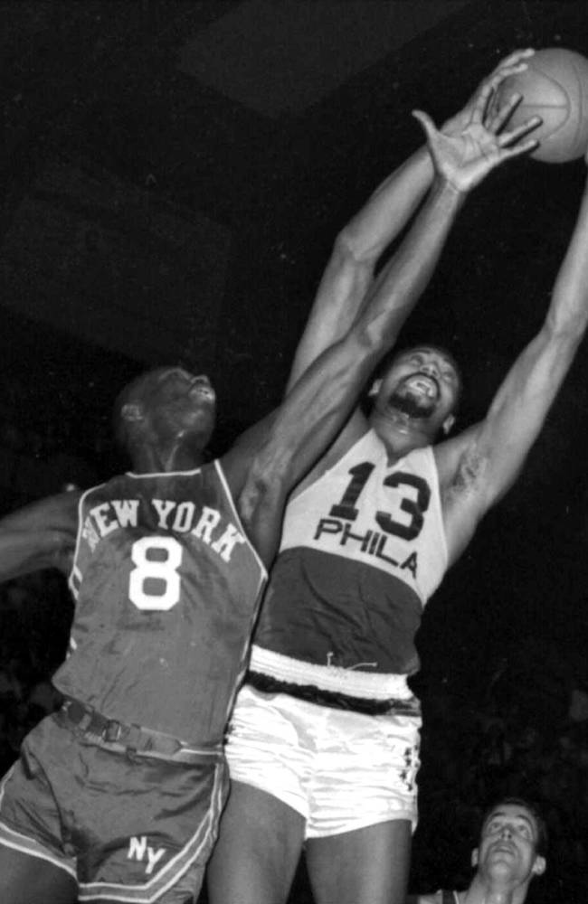 In this March 18, 1966, file photo, Philadelphia 76ers' Wilt Chamberlain, right, grabs a rebound over New York Knicks' Walt Bellamy. Bellamy, the Hall of Fame center who averaged 20.1 points and 13.7 rebounds in 14 seasons in the NBA, died Saturday, Nov. 2, 2013. He was 74. The Atlanta Hawks confirmed the death, but didn't provide details. (AP Photo)