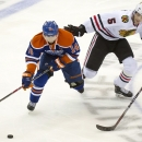 Edmonton Oilers Jordan Eberle, left, battles for the puck with Chicago Blackhawks David Rundblad during second period NHL pre-season action in Saskatoon, Saskatchewan, Sunday, Sept 28, 2014. The Associated Press