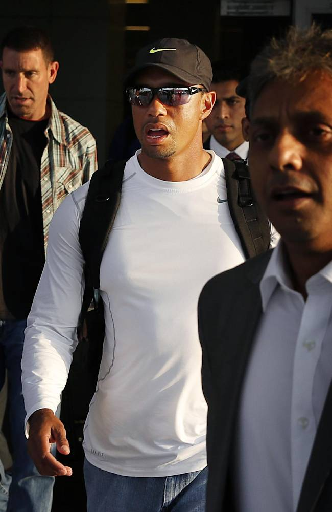 Tiger Woods, center, arrives at the Indira Gandhi International airport, in New Delhi, India, Monday, Feb. 3, 2014. Woods arrived Monday on his first visit to India to play an exhibition with a top business executive. (AP Photo /Manish Swarup)