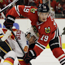 Chicago Blackhawks center Jonathan Toews (19) battles for the puck against Calgary Flames center Josh Jooris (86) during the first period of an NHL hockey game in Chicago, Sunday, Dec. 14, 2014 The Associated Press