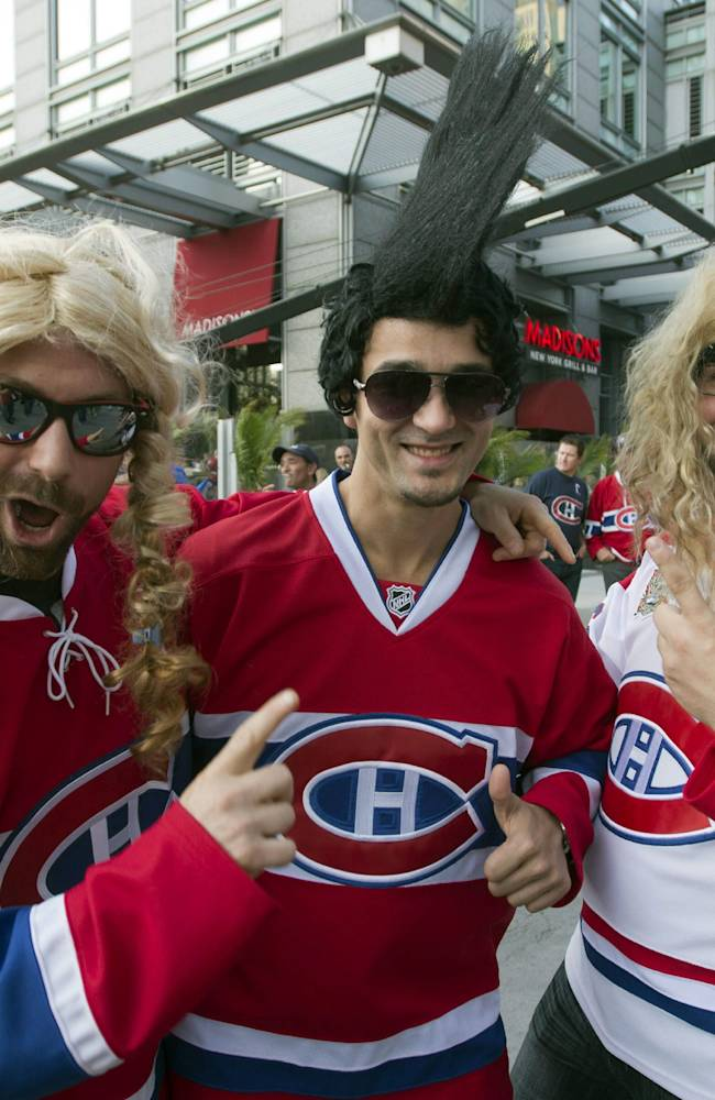 Montreal Canadiens fans, from left, Jonathan Lamothe, Miguel Plourde and Dominique Petit gesture and wear funny wigs as they take part in pregame festivities before the season-opening NHL hockey game between the Toronto Maple Leafs and the Montreal Canadiens, Tuesday, Oct. 1, 2013, in Montreal