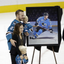 San Jose Sharks' Scott Hannan, left, is presented with a painting of his likeness to commemorate Hannan's 1,000th game before an NHL hockey game against the New York Islanders Saturday, Nov. 1, 2014, in San Jose, Calif. Pictured with Hannan are wife Kris