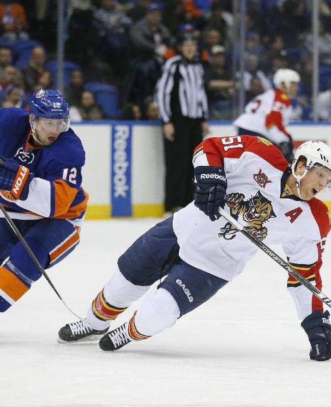 New York Islanders left wing Josh Bailey (12) trips Florida Panthers defenseman Brian Campbell (51) during the second period of an NHL hockey game at Nassau Coliseum in Uniondale, N.Y., Tuesday, April 1, 2014. Bailey received a two-minute penalty. The Islanders won 4-2
