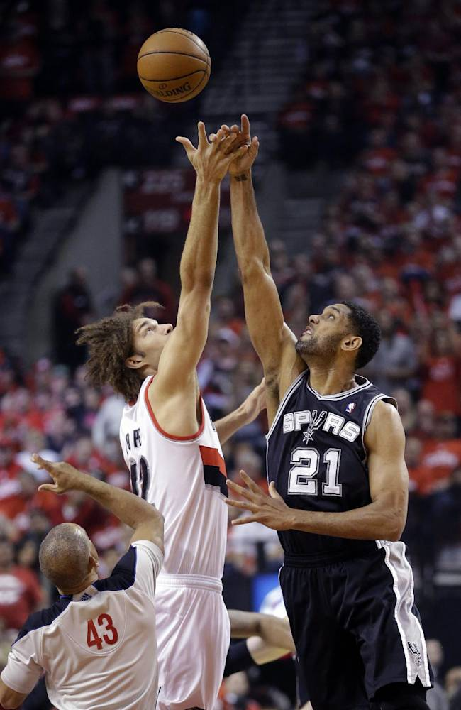 Portland Trail Blazers' Robin Lopez, left, and San Antonio Spurs' Tim Duncan (21) battle for the tipoff in the first quarter during Game 3 of a Western Conference semifinal NBA basketball playoff series Saturday, May 10, 2014, in Portland, Ore